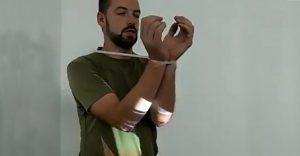 Muž ukazuje, ako jednoduchým spôsobom vymaniť svoje ruky zo zovretia eska pásky